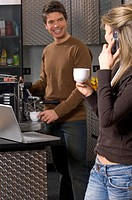 young woman and man making coffee in kitchen