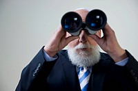 Senior citizen with a beard, wearing a suit, looking through a pair of binoculars