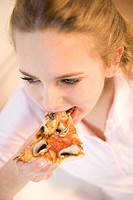 Teenage girl eating a slice of pizza