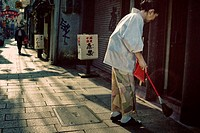 Japanese woman sweeping the street wearing a Kimono Chinatown,Nagasaki,Japan