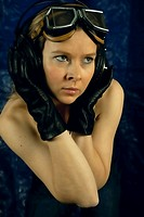 Woman listening to music with headphones, with motorcycle goggles and leather gloves