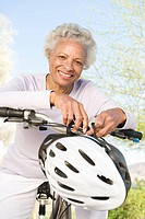 Senior woman leans on handlebars of mountain bike