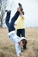 Two boys practicing a handstand in a meadow