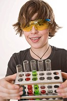 Boy wearing safety glasses, holding a stand with test tubes