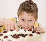 Boy eating a piece of Black Forest Cake secretively