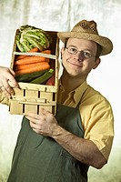 Greengrocer, portrait of a man with straw hat and basket full of vegetables