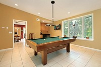 Pool room in suburban home with kitchen view