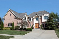 Large suburban brick home with arched entry