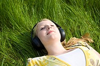 Portrait of a sleeping blond girl lying in the grass wearing headphones