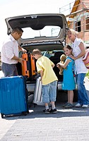 Family stowing the suitcases in the car