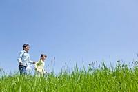 Japan, Tokyo Prefecture, Children running in meadow, side view