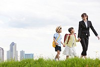 Japan, Tokyo Prefecture, Mother and children walking through meadow, skyscrapers in background