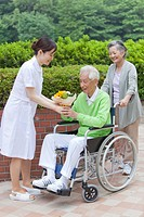 Japan, Tokyo Prefecture, Female nurse giving flower bouquet to senior man sitting on wheelchair