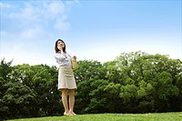 Japan, Osaka Prefecture, Businesswoman standing in grass, using mobile phone