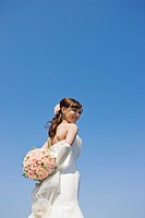 a Japanese bride holding bouquet of flowers behind her back
