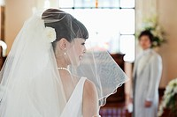 bride smiling while groom standing in the background
