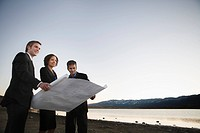 2 men and a woman examine plans by lake