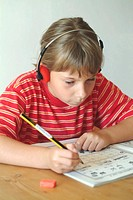Kind macht hausaufgaben mit Musik/ child does her homework listening to music