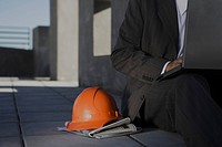 Man sitting on sidewalk using laptop, orange hard hat set on newspaper at side