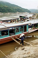 Cargo boats are unloaded at the sand bank on the Mekong river at Pak Beng in Laos in south east Asia