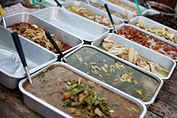 Trays of food for sale in a market in Luang Prabang, Laos