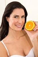 Portrait of woman holding orange