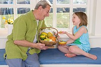Grandfather and granddaughter with basket of wooden Easter eggs