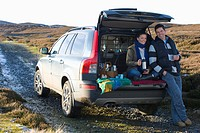 Couple enjoying picnic in back of car on remote road