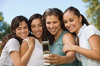 Woman using mobile phone photographing self with three women.