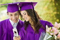 Two graduates looking at cell phone outdoors