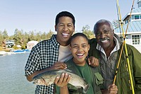 Male members of three generation family showing fish smiling portrait