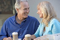 middle_aged Couple sitting outdoors on Shopping Trip looking in eyes