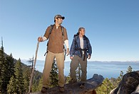 Two male hikers on log near forest (thumbnail)