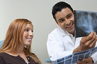 Dentist and patient examining X-rays (thumbnail)