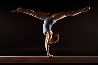 Gymnast 13-15 doing split handstand on balance beam side view (thumbnail)