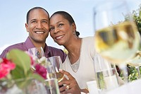 Elegant couple cheek to cheek holding wine glasses at garden party table (thumbnail)
