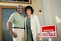 Middle_aged couple standing in front of new home portrait