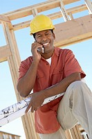 Man on building site on cell phone (thumbnail)