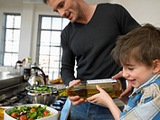 Father and son 3-4 preparing salad in kitchen (thumbnail)