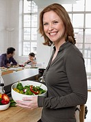 Woman holding salad bowl in kitchen portrait