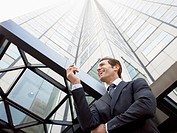 Businessman reading message on phone outside office low angle view