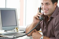 Businessman using telephone at desk in office (thumbnail)