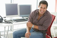 Businessman smiling by computers in office portrait (thumbnail)