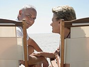 Senior couple on sunloungers on beach back view