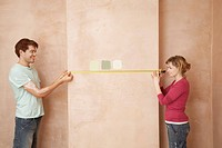 Couple holding measuring tape to wall in unrenovated room