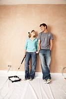 Couple standing with paint roller in unrenovated room