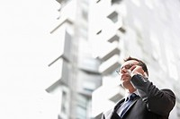 Businessman using mobile phone in front of tall building low angle view (thumbnail)
