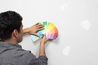 Man holding paint colour samples against interior wall back view