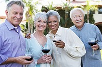 Middle-aged Friends standing outside Drinking Wine from wineglasses (thumbnail)