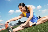 Female athlete stretching on field (thumbnail)